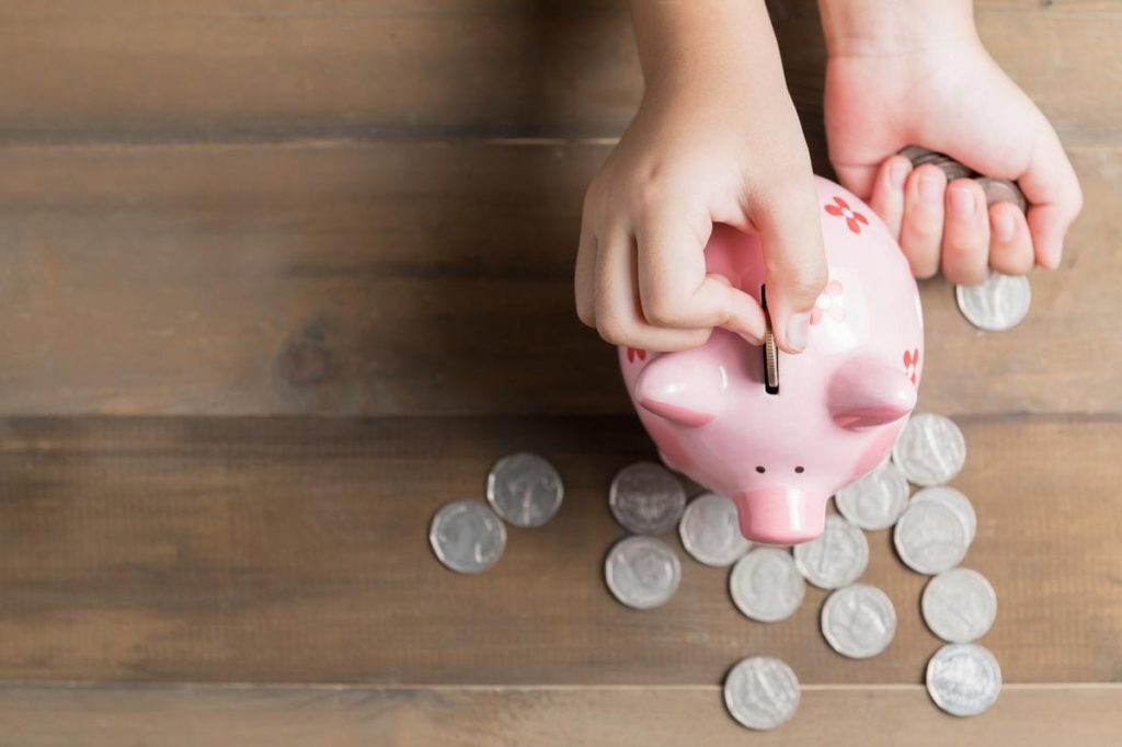 Image showing someone putting money in a piggy bank